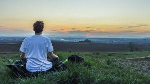 geführte Meditation. meditierender Junge, der in der Natur sitzt und Achtsamkeit lernt
