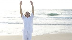 Mann am Meer, Hände hebend. Führt gerade seine Tai Chi und Qi Gong übung aus.