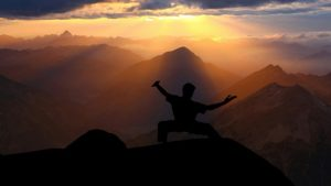 Tai Chi oder TaiChi Lehrer in der Natur zwischen Bergen beim Sonnenuntergang